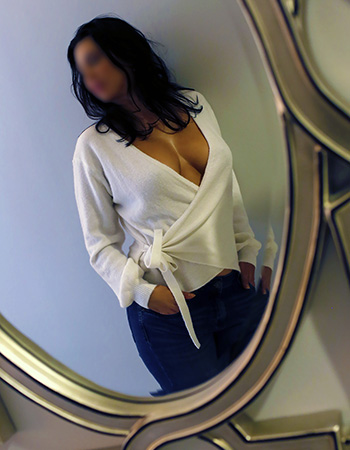 Amaia X in Raleigh, wearing low-cut blouse standing in front of a mirror