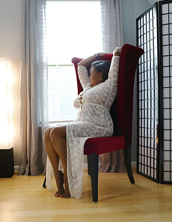 Ebony escort Ms. Phemie sitting in a red chair next to a window, wearing a sheer white dress