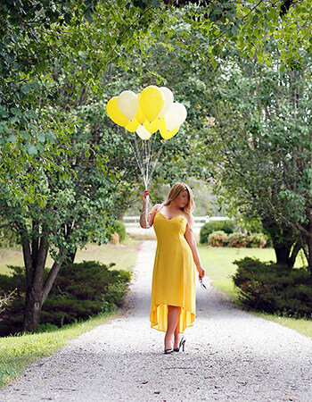 Minneapolis escort Lexy Jorden standing on a gravel road wearing a yellow dress and holding yellow ballons