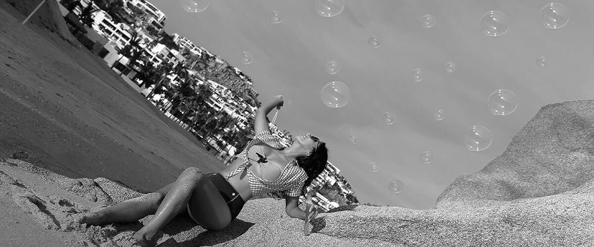 Amaia X wearing a sexy two-piece outfit and blowing bubbles during a photo shoot on the beach in Mexico